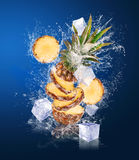 Sliced Pineapple in water splashes with ice cubes Stock Images