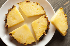 Sliced pineapple on white ceramic plate. On wooden table, closeup shot, selective focus Royalty Free Stock Photos