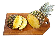 Sliced pineapple on wooden board isolated on white Royalty Free Stock Photos
