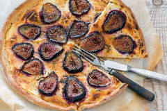 Sliced pizza with figs, fork and knife. Stock Photo