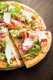 Sliced pizza with prosciutto parma ham, arugula (salad rocket) and parmesan on dark wooden background close up Royalty Free Stock Photography