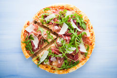 Sliced pizza with prosciutto (parma ham), arugula (salad rocket) and parmesan on blue wooden background Royalty Free Stock Photos