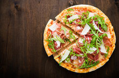 Sliced pizza with prosciutto (parma ham), arugula (salad rocket) and parmesan on dark wooden background Royalty Free Stock Photography