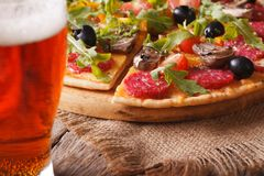 Sliced pizza with rucola close-up and beer, horizontal Royalty Free Stock Images