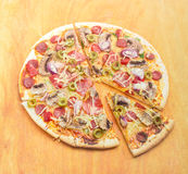 Sliced pizza with sausage, mushrooms and olives on cutting board Royalty Free Stock Photos