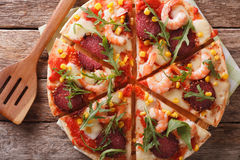 Sliced pizza with shrimp, salami, cheese and arugula closeup. ho. Sliced pizza with shrimp, salami, cheese and arugula close-up on a wooden board. horizontal royalty free stock photos