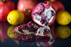 Sliced Pomegranate with arils on black glass stock photos