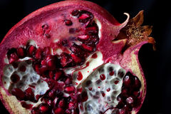 Sliced Pomegranate with arils on black glass Royalty Free Stock Photo
