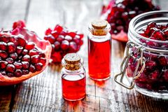 Sliced pomegranate and extract in glass on wooden background. Close up royalty free stock image