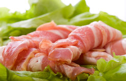 Sliced pork with bacon, lettuce and herbs. Bacon and pork meat with salad Stock Image