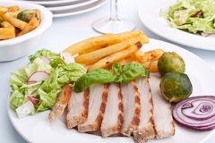 Sliced pork chops with fries and brussels sprouts Stock Photo