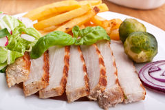 Sliced pork chops with fries and brussels sprouts Royalty Free Stock Photo