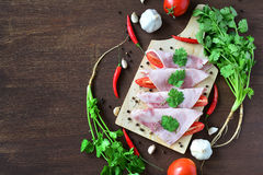 Sliced pork ham with vegetable on wooden background. Stock Image