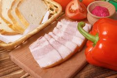 Sliced pork jowl bacon closeup with bread, pepper, tomatoes and horseradish sauce. On wooden plate for cooking stock photos