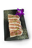 Sliced pork meat with onion on black plate. Deliciously Stock Image