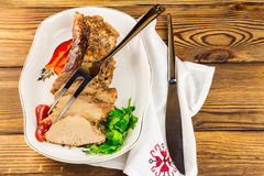 Sliced pork meat with parsley and tomato sauce in plate, knife and fork on napkin, wooden background Stock Image