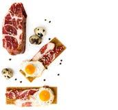 Sliced pork neck and fried quail eggs on rye cracker on white background. royalty free stock image