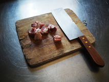 Sliced pork ribs and knife laying on cutting board Stock Photo