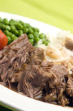 Sliced pot roast dinner. Sliced pot roast beef dinner with peas mashed potatoes and gravy royalty free stock photo