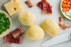 Sliced potato and bacon with knife,potato ready to be filled with bacon. Stock Photography