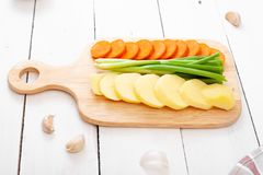 Sliced potatoes, carrot pieces and green onions on a cutting board - fresh vegetables on a light wooden background. Rustic style royalty free stock photo