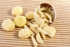Sliced potatoes. Close up view of some sliced potatoes isolated on bamboo background royalty free stock photography