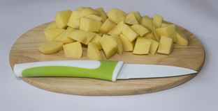 Sliced potatoes on a cutting board with a knife. Group cubes of potatoes on wooden board with knife Stock Image
