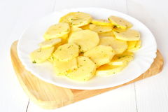 Sliced potatoes with spices on a white plate on a board. Cut potatoes. Raw cut potatoes with spices. Raw potatoes with spices. Potatoes prepared for . Sliced Stock Photos