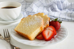 Sliced pound cake. Sliced delicious pound cake with fresh strawberries and icing sugar for breakfast served with hot espresso in white cup royalty free stock photos