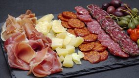 Sliced prosciutto, cheese and salami sausage on stone serving board. Video of sliced prosciutto, cheese and salami sausage on stone serving board stock footage