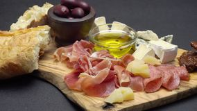 Sliced prosciutto, cheese and salami sausage on a wooden board. Sliced prosciutto, cheese and salami sausage on a wooden cutting board stock video footage