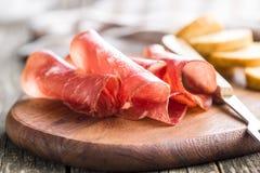 Sliced prosciutto crudo. Sliced prosciutto crudo on cutting board Stock Image