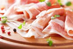 Sliced prosciutto ham on chopping board with oregano and pepper Stock Photos
