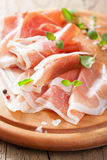 Sliced prosciutto ham on chopping board with oregano and pepper. Sliced prosciutto ham on a chopping board with oregano and pepper Stock Image