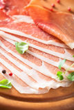 Sliced prosciutto ham on chopping board with oregano and pepper Stock Images