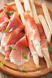 Sliced prosciutto ham and grissini bread sticks Stock Photos
