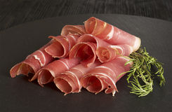 Sliced Prosciutto ham, wooden background, rosemary Stock Photography