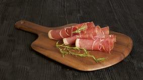 Sliced Prosciutto ham, wooden background, rosemary Stock Photo