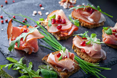Sliced prosciutto with herbs and pomegranate seeds Stock Photo