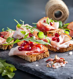 Sliced prosciutto with herbs and pomegranate seeds royalty free stock photography