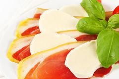 Sliced prosciutto and mozzarella with basil and tomatoes Stock Images