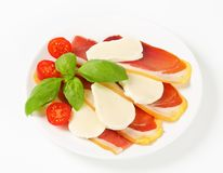 Sliced prosciutto and mozzarella with basil and tomatoes Stock Photos