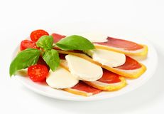 Sliced prosciutto and mozzarella with basil and tomatoes Royalty Free Stock Photo