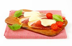 Sliced prosciutto and mozzarella with basil and tomatoes Royalty Free Stock Photography