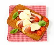 Sliced prosciutto and mozzarella with basil and tomatoes Stock Photography