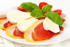 Sliced prosciutto and mozzarella with basil and tomatoes Royalty Free Stock Image