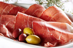 Sliced prosciutto with olive fruit Royalty Free Stock Images