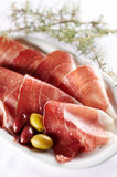 Sliced prosciutto with olive fruit Stock Photography