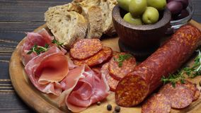 Sliced prosciutto and salami sausage on a wooden board. Sliced prosciutto and salami sausage on a wooden cutting board stock video