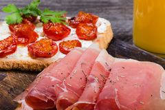 Sliced prosciutto on toasted bread royalty free stock photography